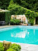 Elongated pool in garden of one-storey country house with small painter's studio surrounded by tall deciduous trees