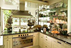 Modern, country-house-style kitchen with extractor hood and collection of crockery on glass shelves to one side; friendly little ceramic pigs on marble worksurface