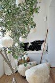 Olivenbaumstamm mit Wollkugeln und Schäfchenhocker vor gemauerter Sitznische mit schwarzweiss gewebten Kelimkissen