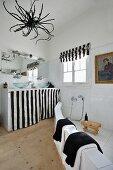 Originelle Badgestaltung mit abgemauertem Duschbereich und textilem Schwarzweissdekor; getrocknete Wurzel als Lampenschirm