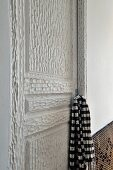 Schwarzweisses Schaltuch am Griff einer kunsthandwerklich bearbeiteten, weiss lackierten Holztür