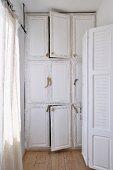 Weiss lackierter Einbauschrank mit naturhaften Holzgriffen in einem schmalen Raum