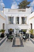 Schwarzweiss gestalteter Innenhof im nordafrikanischen Stil mit Korbstühlen an Mosaiktisch und Palmentöpfen
