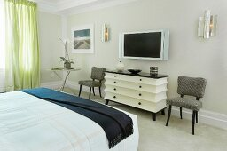 Bed room with black and white, post-modern chest of drawers between upholstered chairs