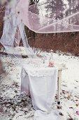 Weisser Tisch mit bodenlanger Tischdecke unter wehenden Chiffonbahnen; auf dem Tisch selbstgemachtes Himbeereis