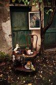 Antiker Tisch und Stuhl vor rustikalen Türen; auf dem Tisch ein angeschnittener Schweinekrustenbraten