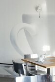 Two place settings for afternoon coffee on designer table in front of photo art with cup motif on white wall
