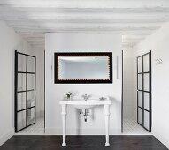 Weisser Vintage Waschtisch am Raumteiler zwischen offenen Glas Sprossentüren mit schwarzem Metallrahmen