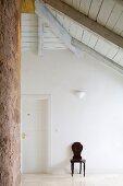 Antiker Stuhl aus dunklem Holz in leerem Dachgeschoss Vorzimmer