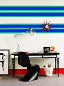 Blue and green horizontal stripes and sunburst clock above black and white work area and bright red skirting board