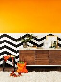 Orange colour gradient on wall above black and white zigzag dado as dynamic background for designer sideboard