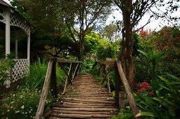 Romantic, old wooden bridge next to pavilion in lush, green garden