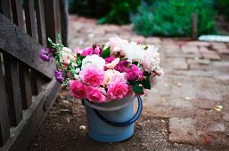 White and pink, cottage-garden bouquet in plastic bucket next to garden gate