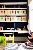 Fabric storage bins with colorful labels in shelves above a writing desk in a children's room