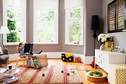 Little boy on a chair with picture book and toys thrown around the room in an elegant bay window with gray walls