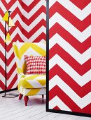 Mini-room with red and white zigzags on the movable walls and yellow and white zigzag armchair