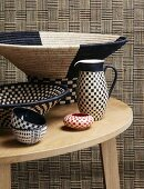 Simple wooden table with assorted, ethnic style, checkerboard wicker weave containers