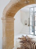 Historical, stone arched doorway and view of zebra-skin rugs