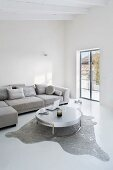 Purist living room in grey and white with designer table on animal-skin rug and corner sofa