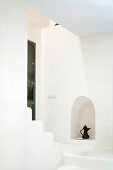 Staircase as minimalist, white spatial sculpture with Oriental teapot in niche