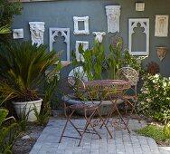 Filigrane Metall Outdoormöbel auf Terrasse und Pflanzen im Topf vor antik stilisierten Rahmen an grauer Hauswand