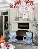 Silver gilt, antique armchairs with shimmering upholstery and chandelier with red crystals in front of open fireplace