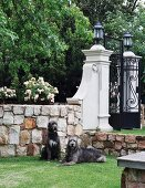 Two dogs in front of stone wall and wrought iron garden gate with decorative masonry pillars