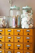 Gifts in large glass jars with lids on antique apothecary cabinet with alphabetically labelled drawers