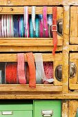 Spools of various ribbons in glass-fronted drawers of vintage cabinet