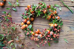 Wreath of rosehips on wooden table