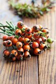 Twigs of rosehips on wooden table