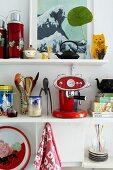 Colourful utensils on white kitchen shelves
