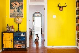 Picture of bullfight above colourful vintage cabinet and antlers on yellow-painted wall; dog on parquet floor in adjoining room