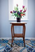Bouquet of lilies on retro side table standing on floor tiles with various Oriental patterns