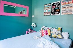 Colourful scatter cushions on bed below pink-framed mirror and artworks with mottoes in English on turquoise wall