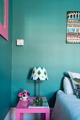 Pink bedside table and lamp with patterned lampshade against turquoise wall