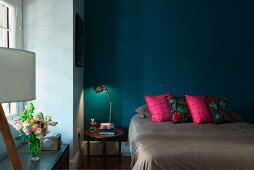 Scatter cushions on double bed and bedside table against petrol blue wall