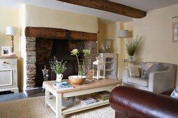 Polstermöbel und Holztisch im Shakerstil vor grossem, offenem Kamin mit Natursteinauskleidung