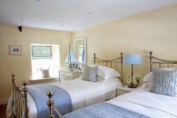 Cremefarbenes Schlafzimmer mit hellblauen Accessoires zu verchromten Landhausbetten