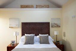 Französisches Bett mit dunklem Kopfteil im Dachgeschoss in elegantem Landhaus Ambiente