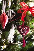Heart-shaped decoration embroidered with the word Noel hanging on Christmas tree decorated in red and white