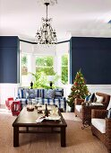 Small Christmas tree between blue and white striped sofa and wicker armchair in front of living room bay window flanked by blue-painted walls