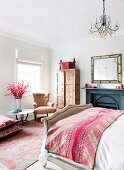 Pink patterned bedspread on antique-style bed in elegant bedroom with upholstered armchair and painted wardrobe in background