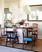 White paper Advent stars above festively decorated table and various chairs