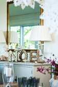 Letters reading NOEL made from stylised, gold fir branches in front of mirror on country-house cabinet