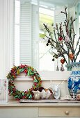 Advent wreath wrapped with colourful ribbons and Christmas tree decorations on branches in ceramic vase