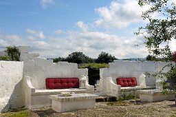 Whitewashed masonry benches and tables with red seating cushions in front of open landscape