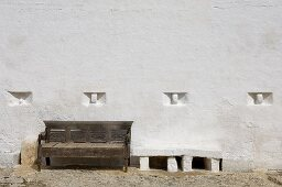 Rustic wooden bench next to masonry bench against white wall