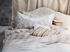 Französisches Bett mit Kopfteil aus Holz und Bettwäsche in verschiedenen Brauntönen