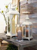 Windlicht mit brennender Kerze vor Laternen im Vintagestil auf rustikaler Holzbank
